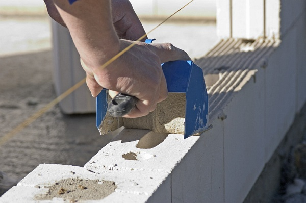 Нанесение клея на блоки при возведении стен.