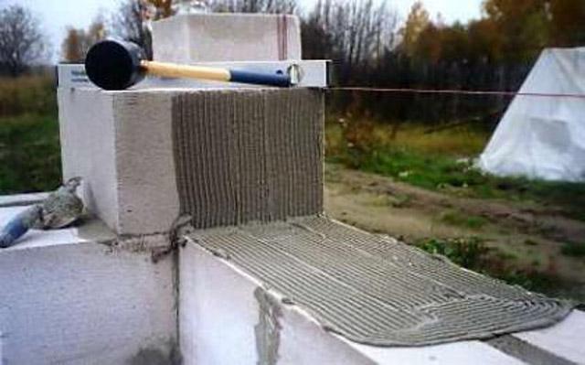 Нанесение клея на поверхность пеноблоков