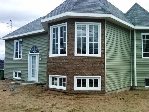 Пеноблочный дом с комбинированной отделкой виниловым и цокольным сайдингом.