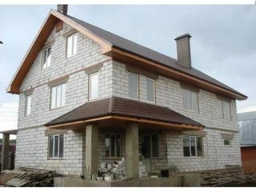 Трехэтажный дом из пеноблоков, построенный с установкой армированных поясов по периметру стен под перекрытиями.