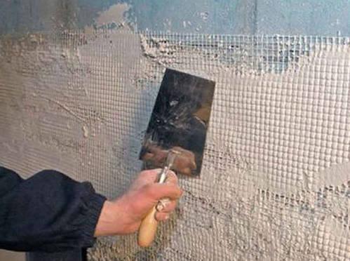 Штукатурную смесь рекомендуется наносить по армирующей сетке, закрепленной на стене из пеноблоков.