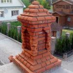 Декоративная колонна стоит на высоком бетонном крыльце