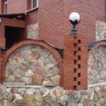 Кирпично-каменный забор с интересными по форме столбами и арками